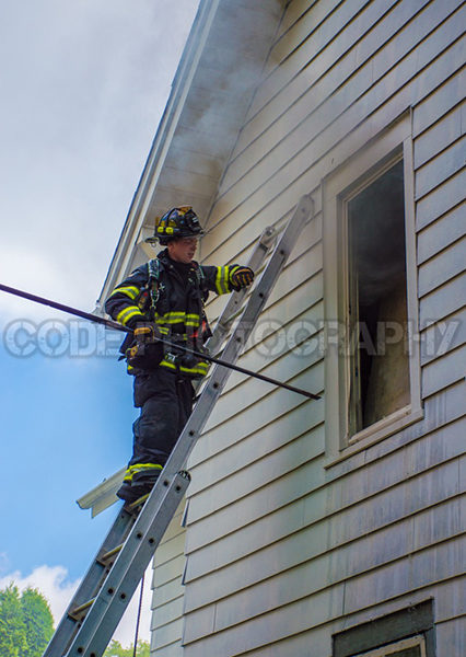 firefighter on ladder venting window