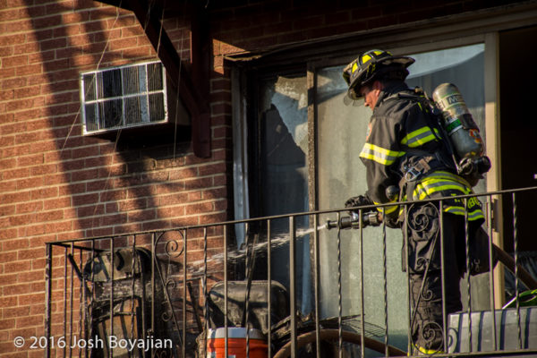firefighter on apartment building patio after fire