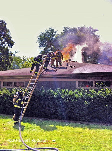 firefighters on house roof with flames