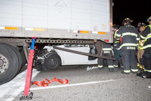 car wedged underneath a truck trailer