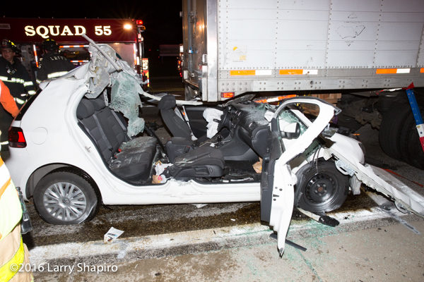 aftermath of accident with a car wedged underneath a truck trailer