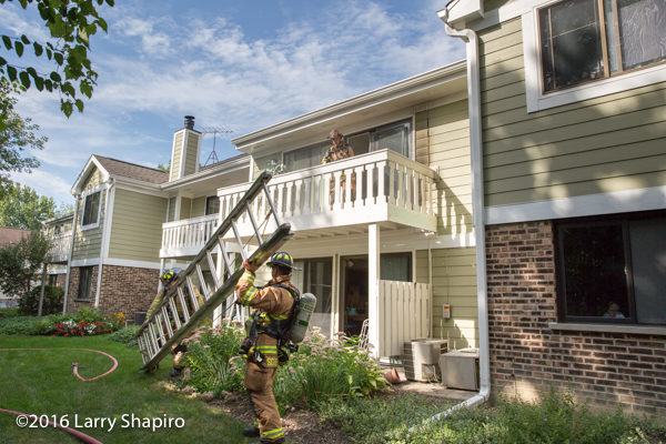 firefighters raise ground ladder to balcony