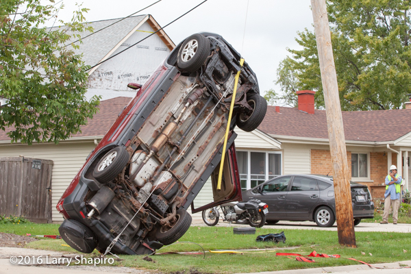 car stuck on utility pole support cables