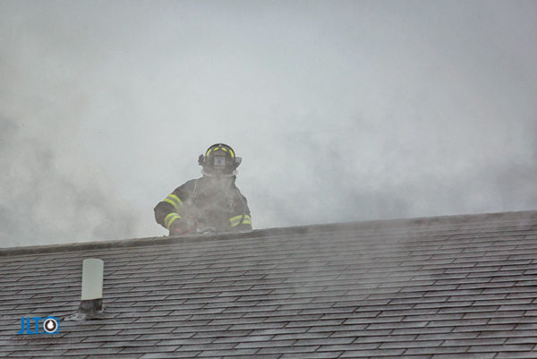firefighter on roof ventilating house during a fire