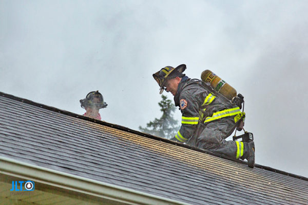 firefighter on roof ventilating house