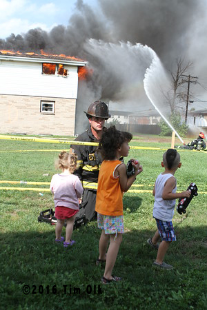 children watch a fire department burn down