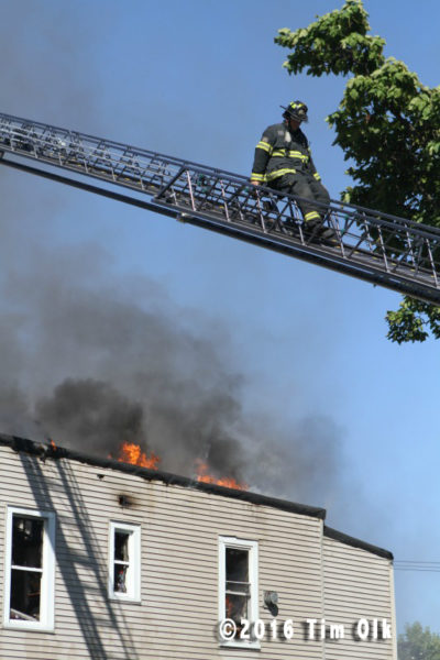 fireman on ladder with flames and smoke