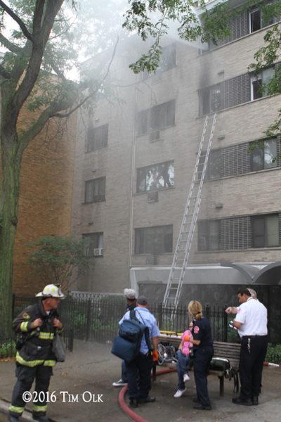 Chicago FD paramedics treat an elderly fire victim at the scene of a fire