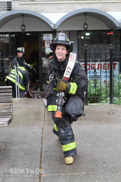 female firefighter pulls hose after a fire