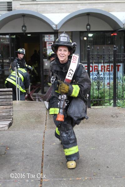 female firefighter pulls hose after a fire