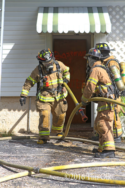 firefighters pulling hose