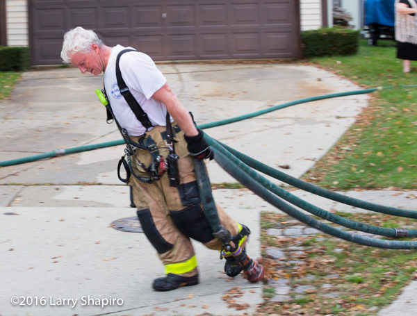 firefighter drags hose after a fire
