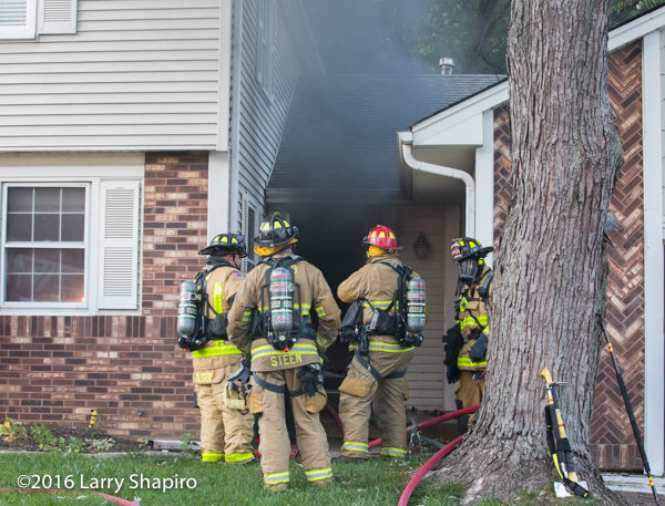 heavy smoke from front door of house on fire