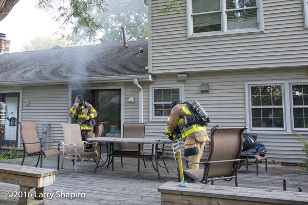 firefighters prepare to enter house on fire