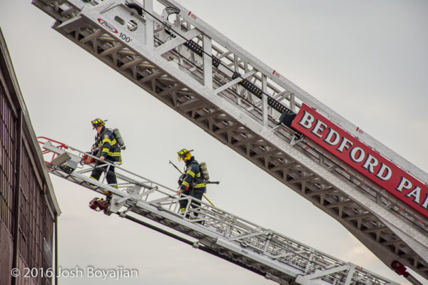 firefighters climb aerial ladder at fire scene