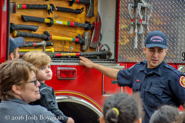 firefighter shows tools to children
