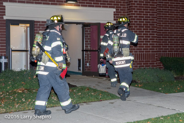 firefighters with tools and PPE enter building