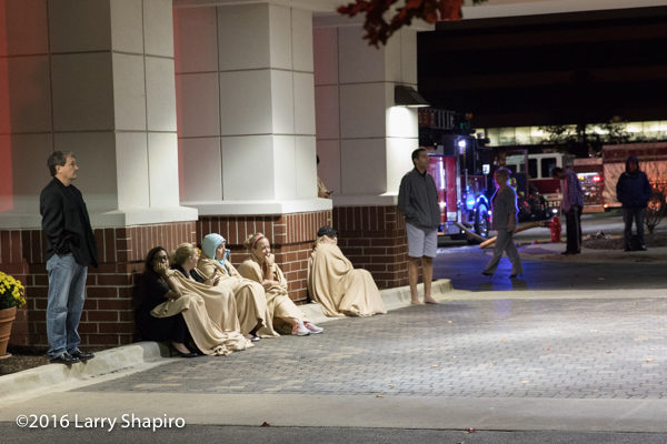 hotel guests wrapped in blankets waiting in the cold
