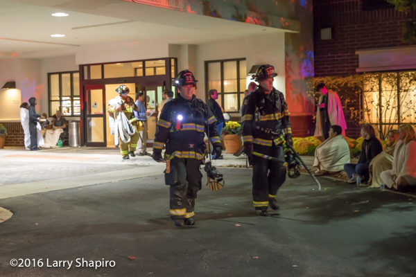 firefighters at night with tools and PPE walking