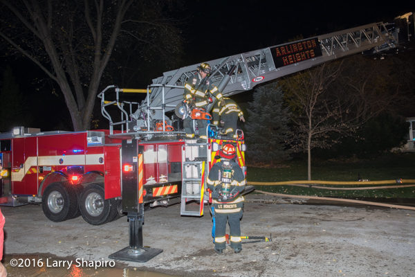 firefighters climb ladder truck with tools during fire