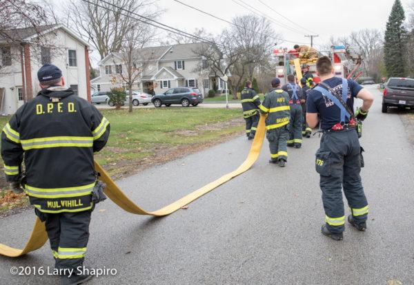 Firefighters load hose onto fire engine