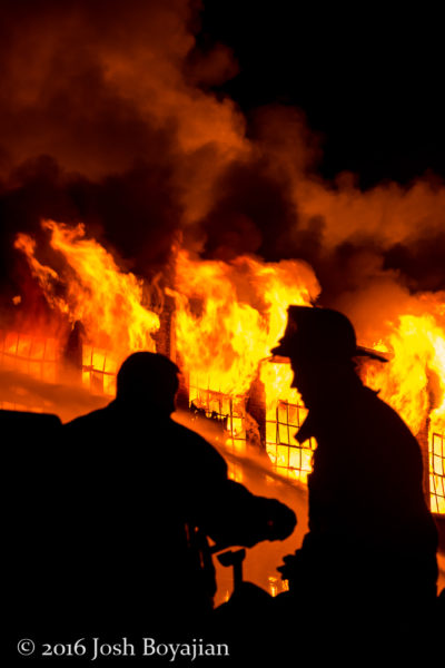 silhouette of firefighters at a massive warehouse fire in Chicago