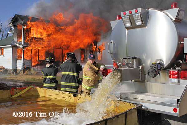 Firefighter dumps water from tender into portable tank