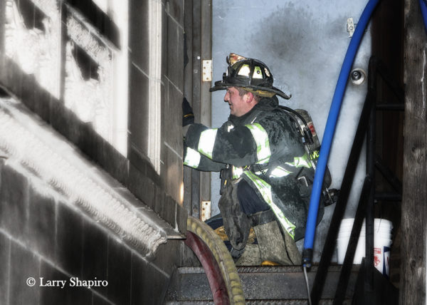 Firefighter guiding hose into doorway