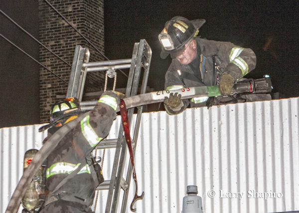Firefighters carry hose line up ladder