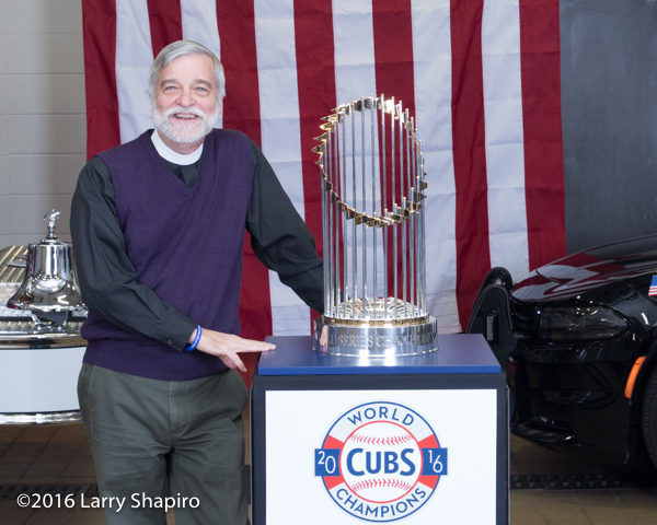 fire department chaplain with the the World Series championship trophy