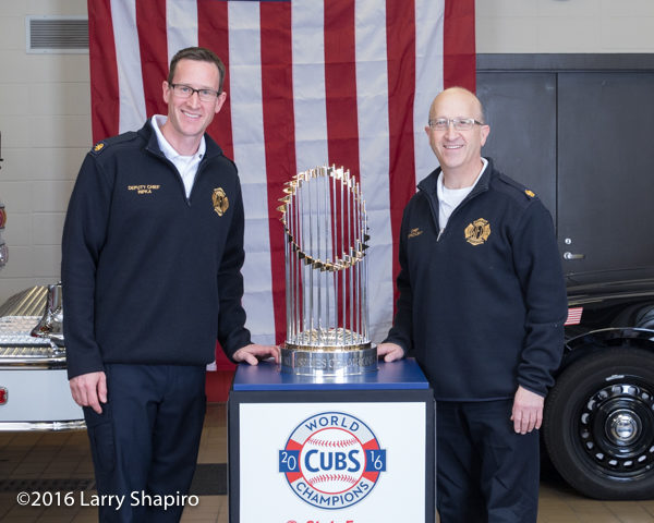 Winnetka fire chief and deputy chief with the the World Series championship trophy