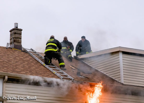 Firefighters on venting a roof during a fire