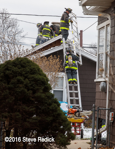 Firefighter brings roof ladder to other Firefighters