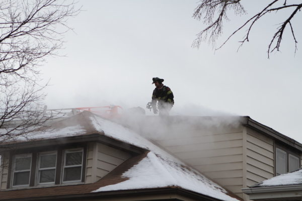 Firefighter on roof with smoke