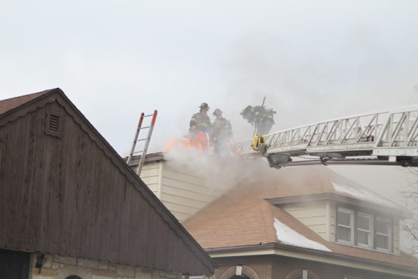 Firefighters vent roof with flames