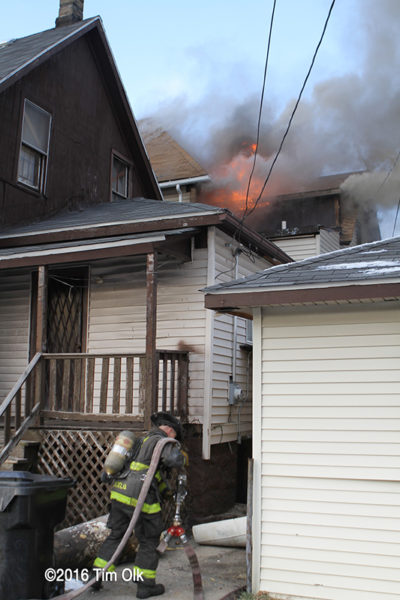 Firefighter dragging a hose line at a house fire