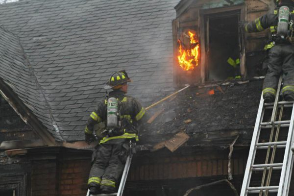 firefighter on ladder at house fire