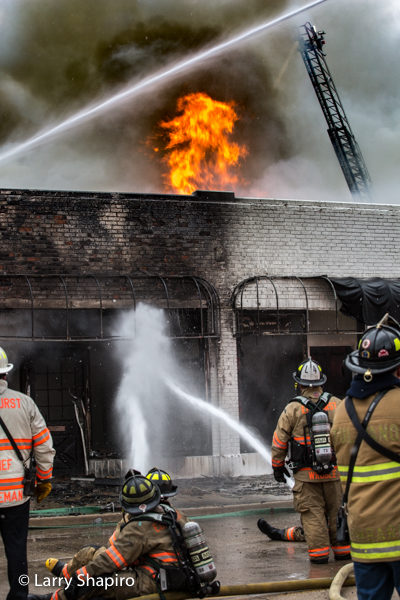 Firefighters pour water into burning store front