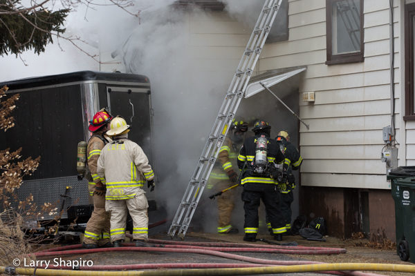 Firefighters at house fire with heavy smoke