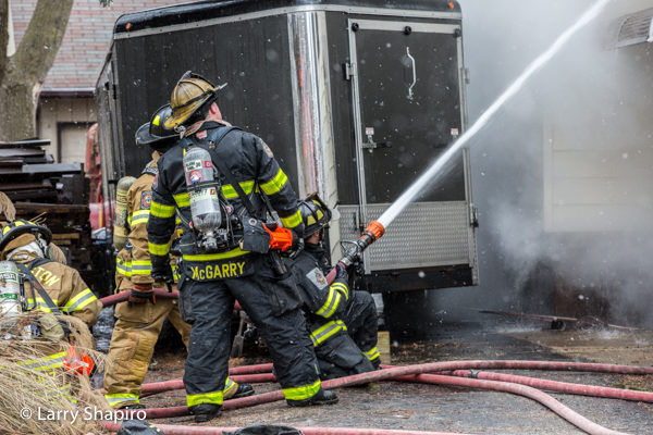 Firefighters with hose line battle house fire