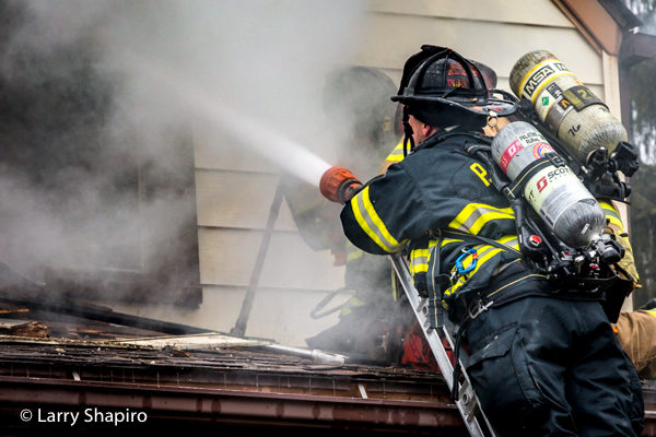 Firefighter with hose line battles house fire