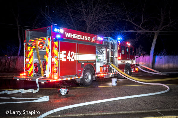 Rosenbauer America Commander fire engine at night fire scene with lights and hose lines
