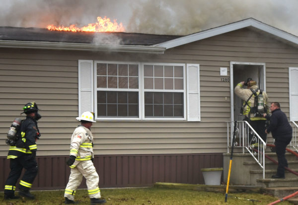 firefighters enter a burning home in a trailer park