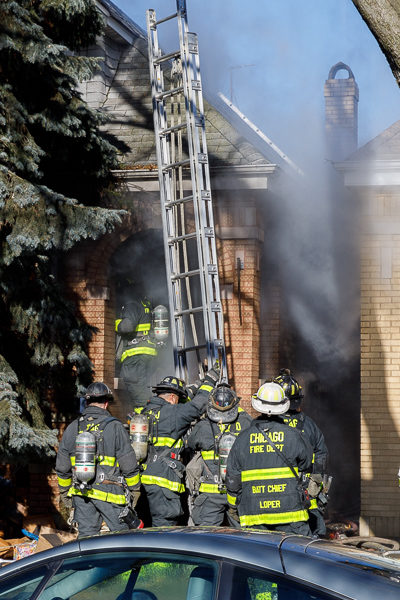 firefighters place ground ladder during fire
