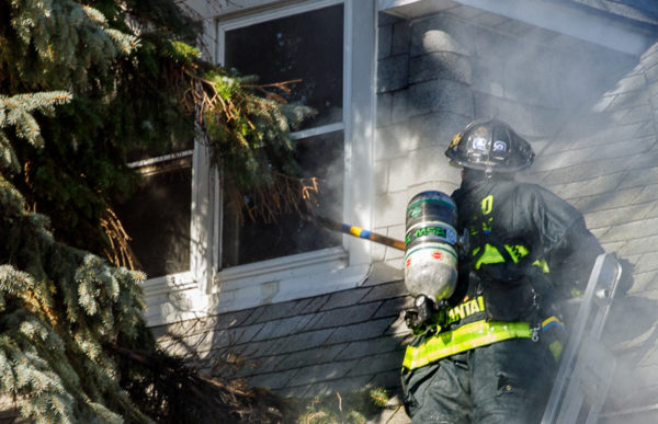 firefighter breaks window with pike pole