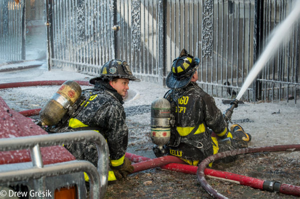 firefighters covered with ice battling fire