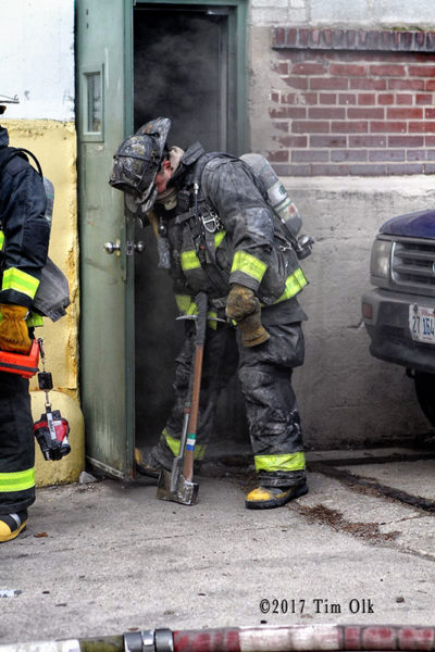 Firefighter props door at warehouse fire