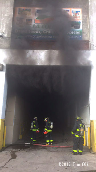heavy smoke pours out of warehouse