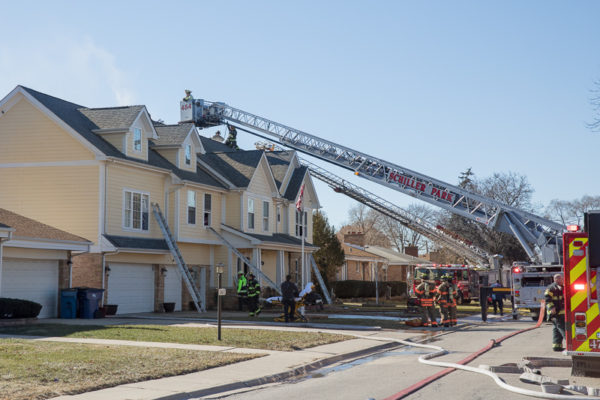 townhouse fire scene with fire trucks
