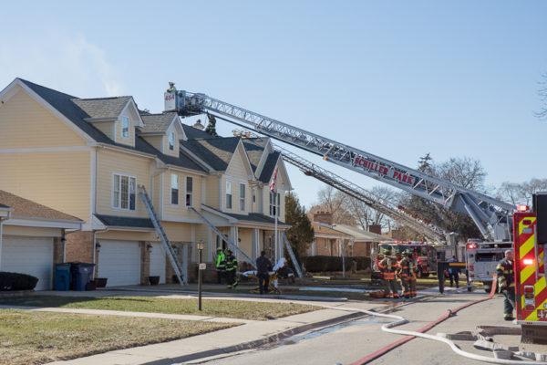 townhouse fire scene with fire trucks